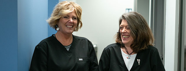 two staff members smiling